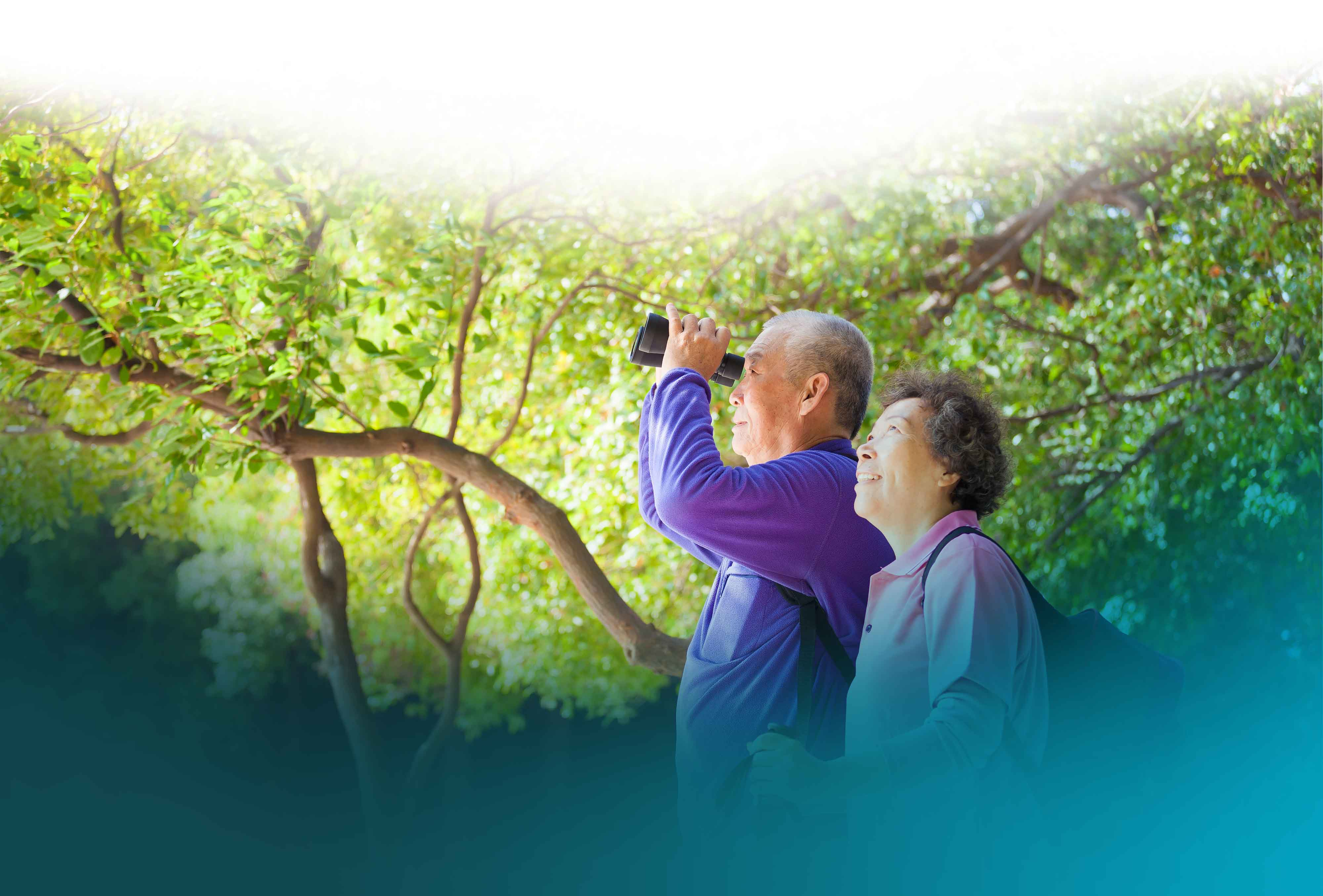 Elderly couple with binoculars in nature